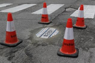 In this Tuesday, June 10, 2014 photo, a pothole filled by mosaic artist Jim Bachor on a street in Chicago is protected by cones until it is ready to be driven on. Bachor has filled seven potholes around the city and marks each one with a mosaic piece. (AP Photo/Stacy Thacker)